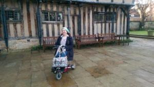 Naomi on her mobility scooter in front of an old building with a row of benches behind her.